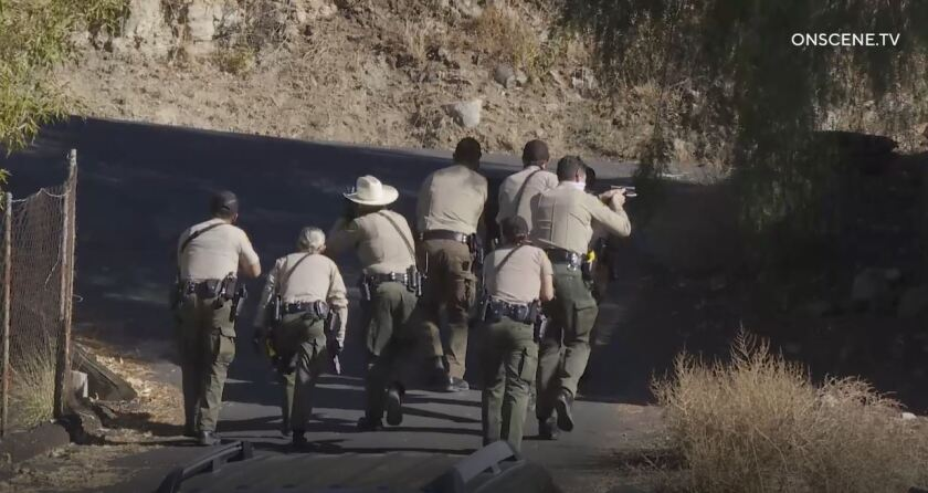 Sheriff's deputies, some with guns drawn, walk up a hill