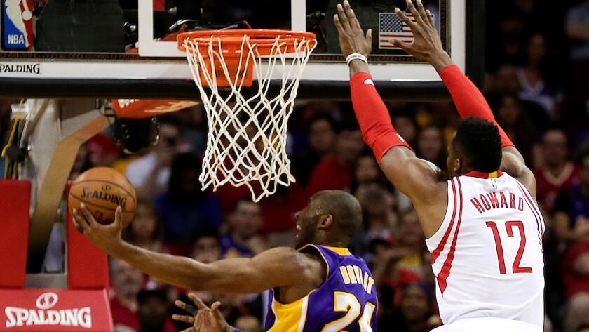 Lakers guard Kobe Bryant tries to score against Rockets center Dwight Howard on a drive down the lane Sunday.