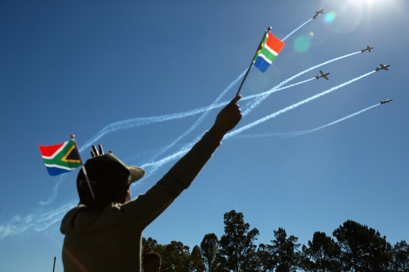 April 27, 2019. A boy waves a flag as members of the South African Airforce Silver Falcons fly over