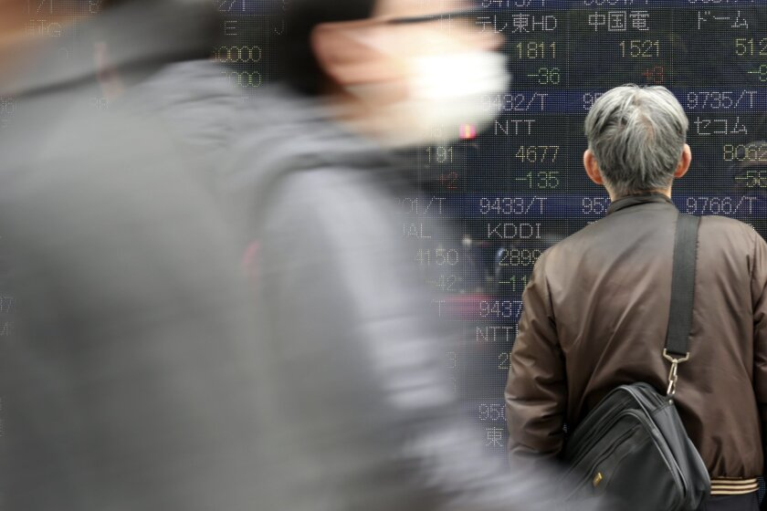 A man looks at an electronic stock board showing Japan's Nikkei 225 at a securities firm in Tokyo, Tuesday, Feb. 23, 2016. Asian stock markets were mostly weaker on Tuesday as the price of crude oil turned lower following a surge overnight. (AP Photo/Eugene Hoshiko)