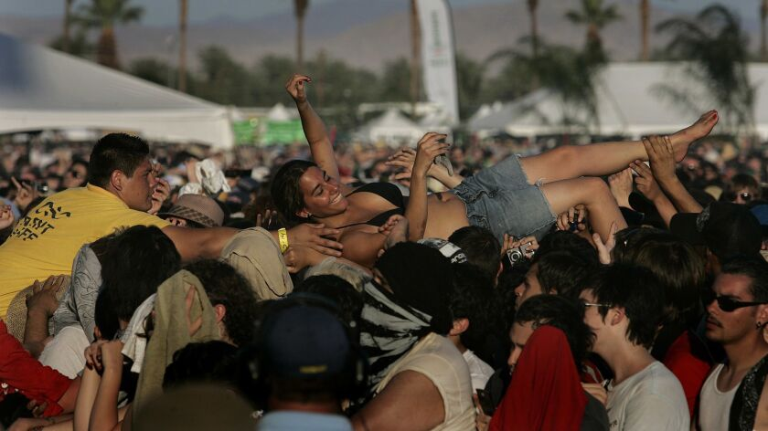A fan is pulled from the crowd during the Arcade Fire performance at Coachella 2007