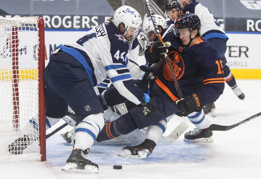 Edmonton Oilers' Josh Archibald (15) is checked by Winnipeg Jets' Josh Morrissey (44) during the second period of an NHL hockey game, Monday, Feb. 15, 2021 in Edmonton, Alberta. (Jason Franson/The Canadian Press via AP)