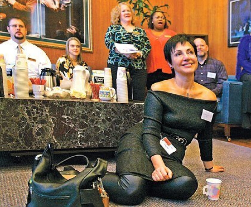 """Soprano Sylvie Valayre (center) listens as San Diego Opera general director Ian Campbell (unseen) talks with the cast of the upcoming production of Puccini's """"Tosca."""" (Howard Lipin / Union-Tribune)"""