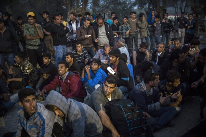 FILE - In this Tuesday, Oct. 20, 2015 file photo people wait to enter a registration center for migrants and refugees in Moria village on the northeastern Greek island of Lesbos, where thousands are camping out in a tent city that has sprung up around the police registration center chosen for the p