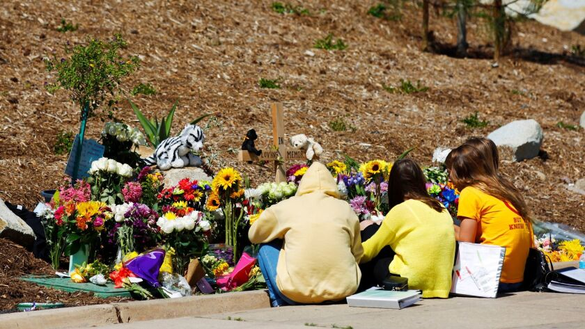 Students wearing yellow shirts for suicide prevention awareness gather at a memorial for a15 year-ol