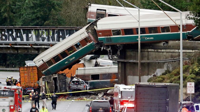 FILE - In this Dec. 18, 2017 file photo, cars from an Amtrak train lie spilled onto Interstate 5 bel