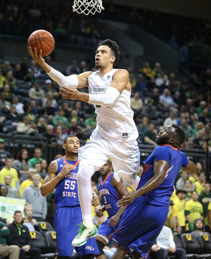 Oregon's Dillon Brooks, center, splits Savannah State's Brian Pearson, left, and Troyce Manassa for a layup during the second half of an NCAA college basketball game Friday, Nov. 20, 2015, in Eugene, Ore. Oregon won 77-59. (AP Photo/Chris Pietsch)
