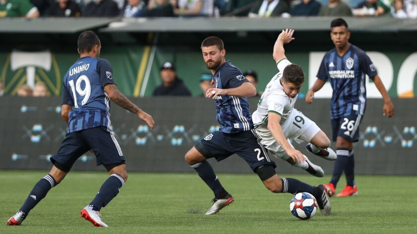 Portland Timbers' Tomas Conechny (19) is knocked off the ball by LA Galaxy midfielder Perry Kitchen