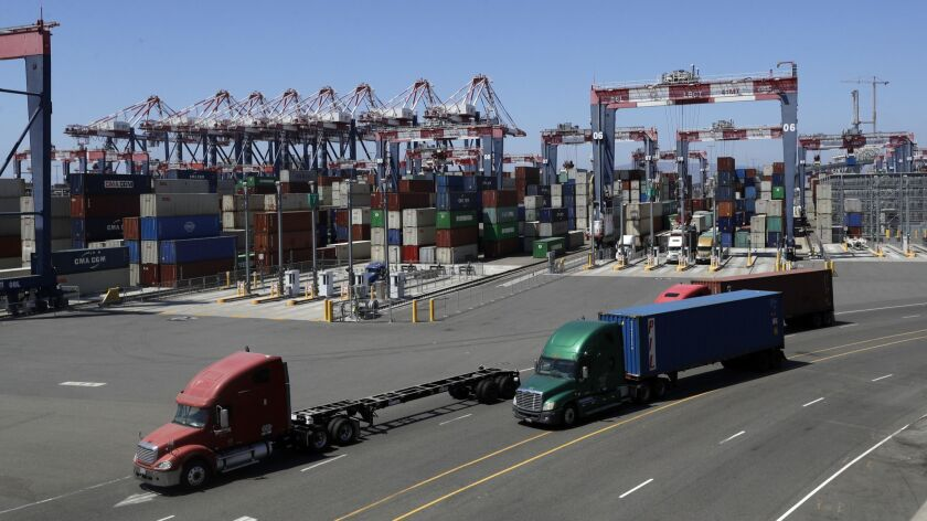 Trucks travel along a loading dock at the Port of Long Beach.