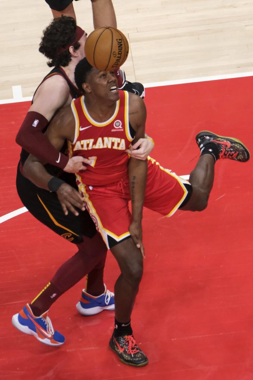 Cleveland Cavaliers forward Cedi Osman, left, fouls Atlanta Hawks forward Nathan Knight, right, during the second half of an NBA basketball game on Sunday, March 14, 2021, in Atlanta. (AP Photo/Ben Gray)