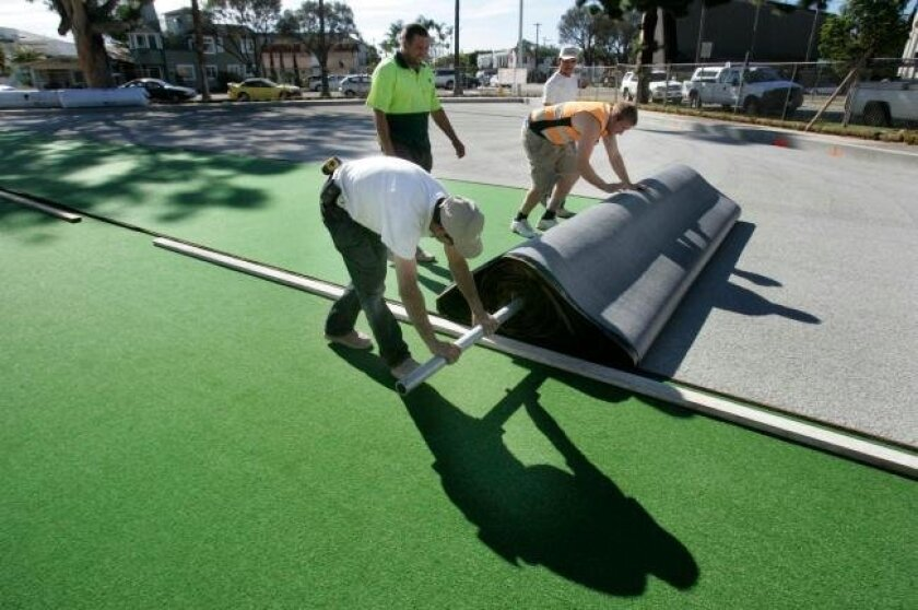 Workers unrolled artificial turf for Coronado's lawn bowling greens. City officials say that while there are more capital costs initially with the $475,000 project, maintenance expenses are much lower with a synthetic turf.