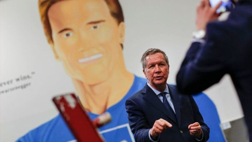With a mural of former California Gov. Arnold Schwarzenegger as a backdrop, Ohio Gov. John Kasich records a message after the event.