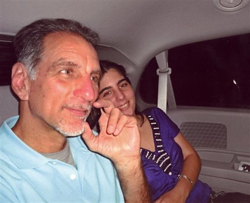 """FILE - In this file photo released on Wednesday Oct. 12, 2011 by the state media Cubadebate website, convicted Cuban agent Rene Gonzalez talks on the phone accompanied by his youngest daughter Ivette, after he was freed from a Florida jail, after serving 13 years of a 15-year sentence, in Marianna, Fla. Gonzalez, one of the so-called """"Cuban Five,"""" will be able to permanently remain in Cuba in exchange for renouncing his U.S. citizenship, a federal judge ruled Friday, May 3, 2013 after U.S. offi"""