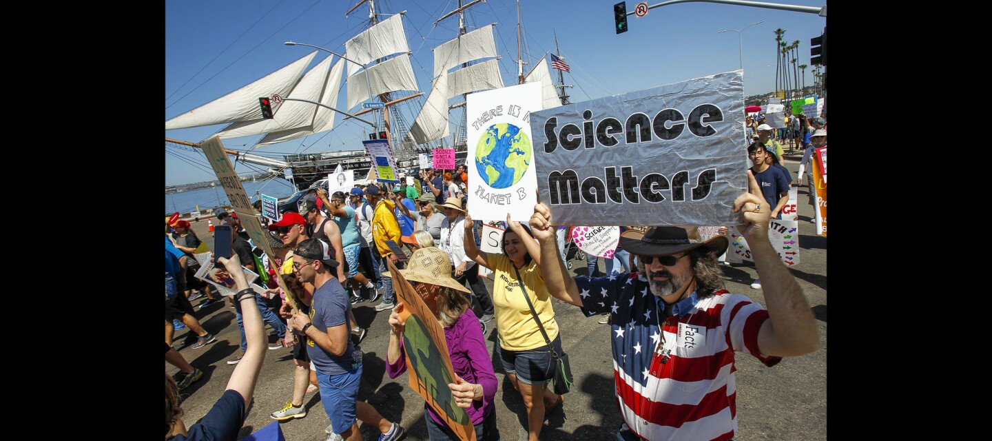 With the Star of India in the background, people begin to march south on North Harbor Drive during the San Diego March for Science.