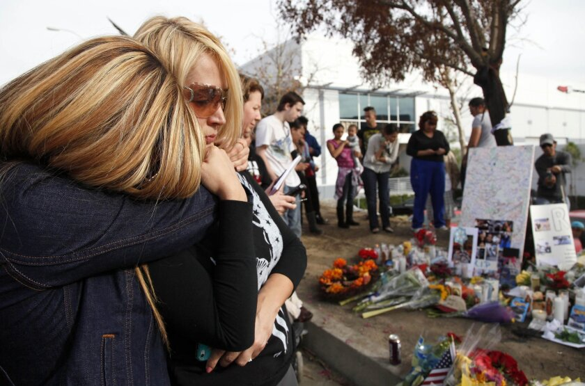 """Marjan Bauman, right, and her daughter Alexandra Bauman join others at the site of the auto crash that took the life of actor Paul Walker and another man, in the small community of Valencia, Calif., Monday, Dec. 2, 2013. The neighborhood where """"Fast & Furious"""" star Walker died in the one-car crash is known to attract street racers, according to law enforcement officials. Walker and his friend and fellow fast-car enthusiast Roger Rodas died Saturday when the 2005 Porsche Carrera GT they were traveling in smashed into a light pole and tree. The two had taken what was expected to be a brief drive away from a charity fundraiser at Rodas' custom car shop in the Southern California community of Valencia, about 30 miles (48 kilometers) northwest of Los Angeles. (AP Photo/Nick Ut)"""