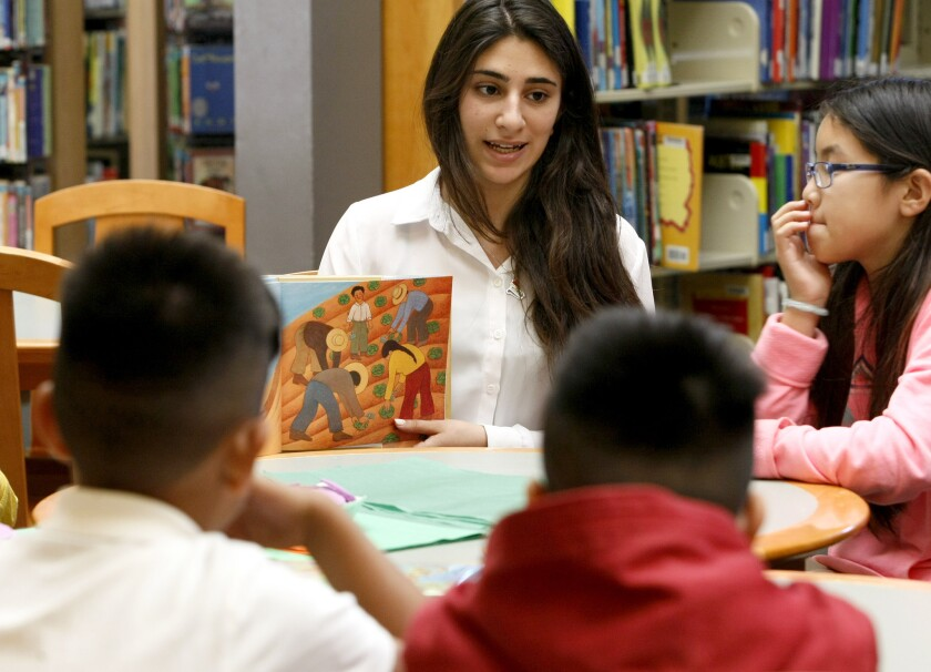In this file photo from March 2014, Noor Atif, then a senior at Clark Magnet High School, reads to school children at Pacific Library in Glendale.