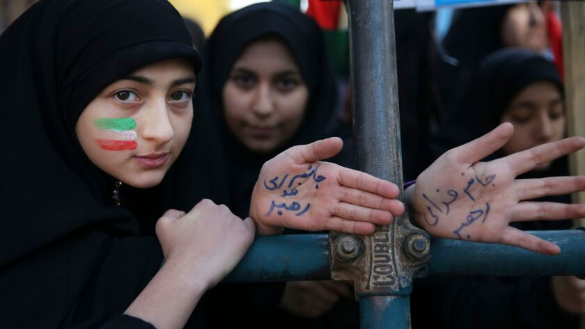 """Two Iranian women, one with her face painted in the colors of the national flag, show their hands with writing in Persian that reads, """"I'm ready to sacrifice myself for the Supreme Leader."""""""