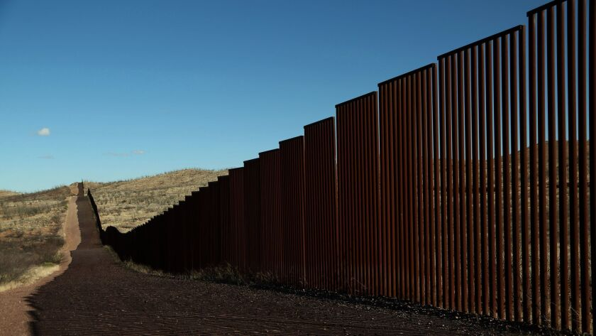 Along the border fence of the United States, left of the fence, and Mexico, on the right, just south of Bisbee in rural Cochise County, Arizona on January 25th. (Los Angeles Times)