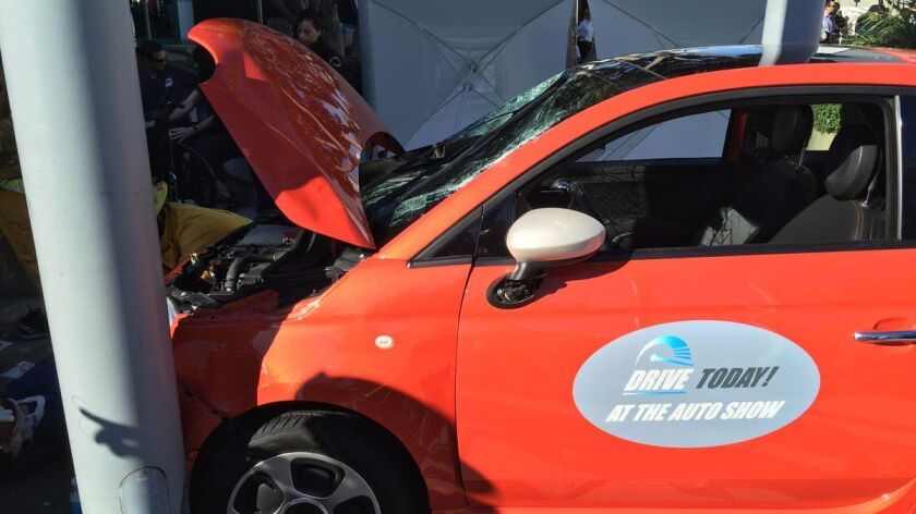 Six people were hurt when a car jumped a curb outside the Los Angeles Auto Show.