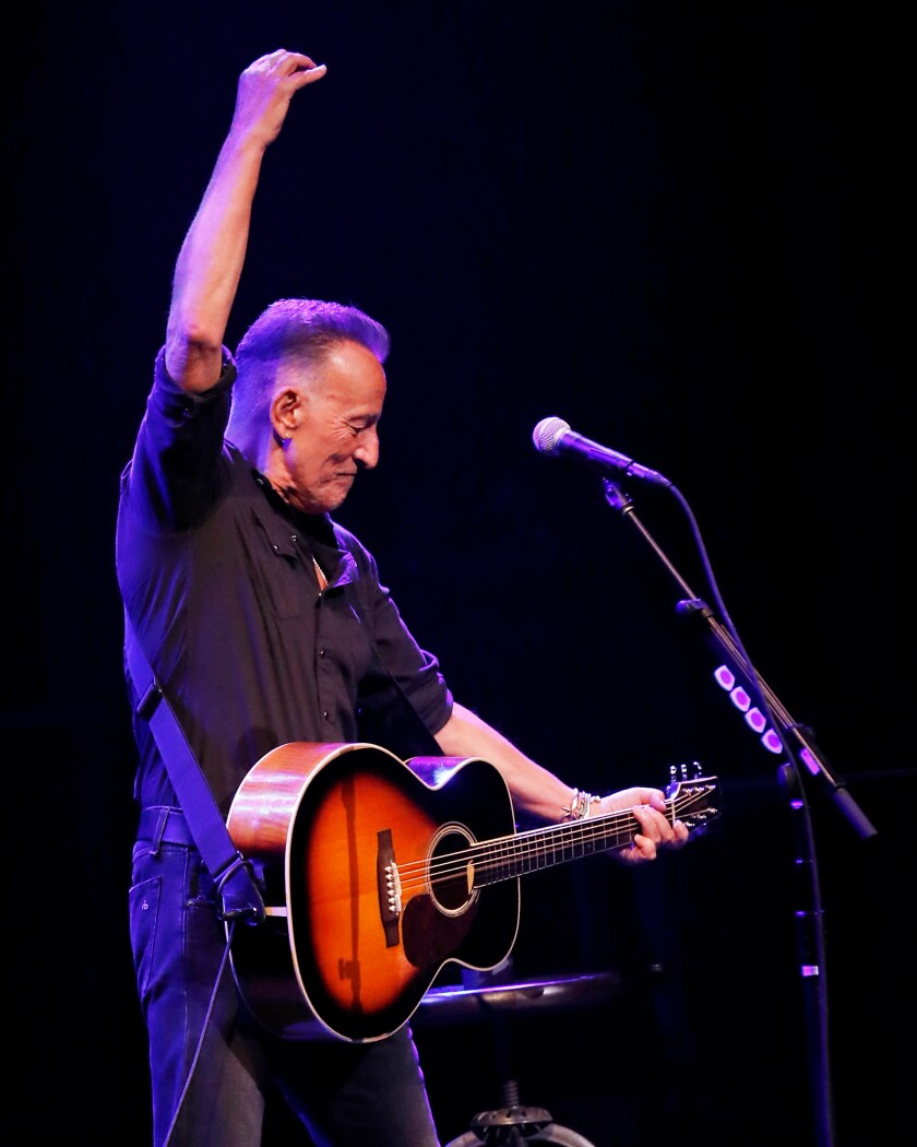 A man holding a guitar stands in front of a microphone stand. His right hand is raised and his left hand holds the guitar