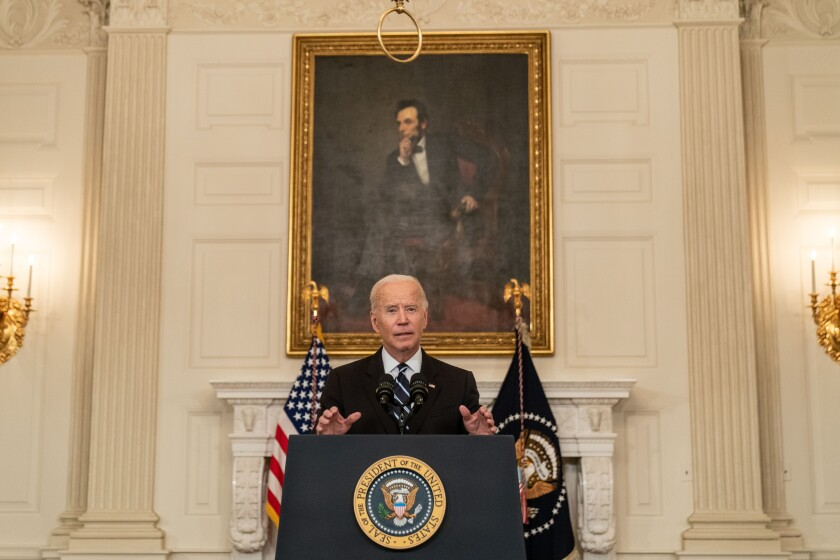 President Biden  speaks at a lectern in front of a painting of Lincoln.