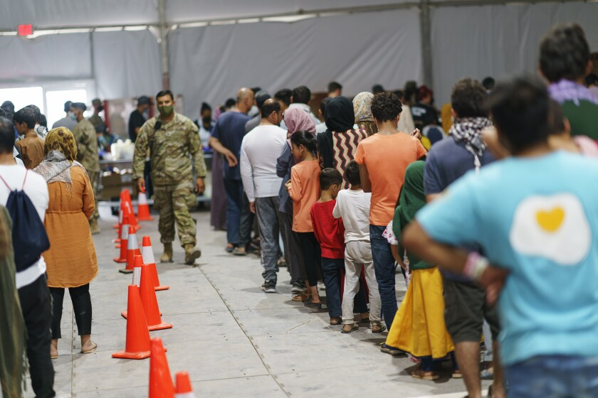 Afghan refugees line up for food in a dining hall at Fort Bliss' Doña Ana Village, in New Mexico,.