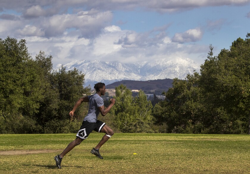 An athlete runs with snow-capped mountains in background
