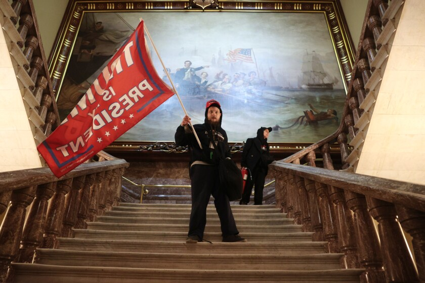 One of many militant Trump supporters who stormed the U.S. Capitol holds a Trump flag on a staircase near the Senate chamber.