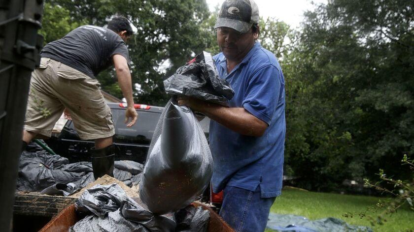 Ruben Lozano, 47, and Javier Escamilla, 27, create makeshift sandbags in an effort to ward off the s