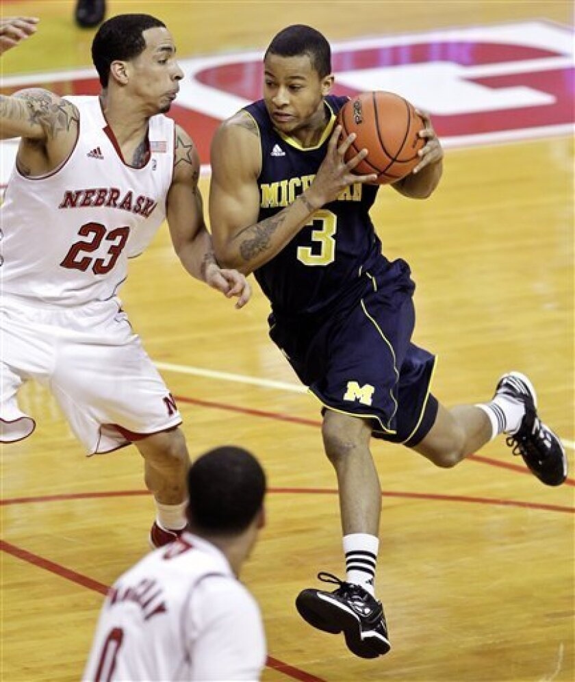 Michigan's Trey Burke (3) drives past Nebraska's Bo Spencer (23) in the first half of their NCAA college basketball game in Lincoln, Neb., Wednesday, Feb. 8, 2012. (AP Photo/Nati Harnik)