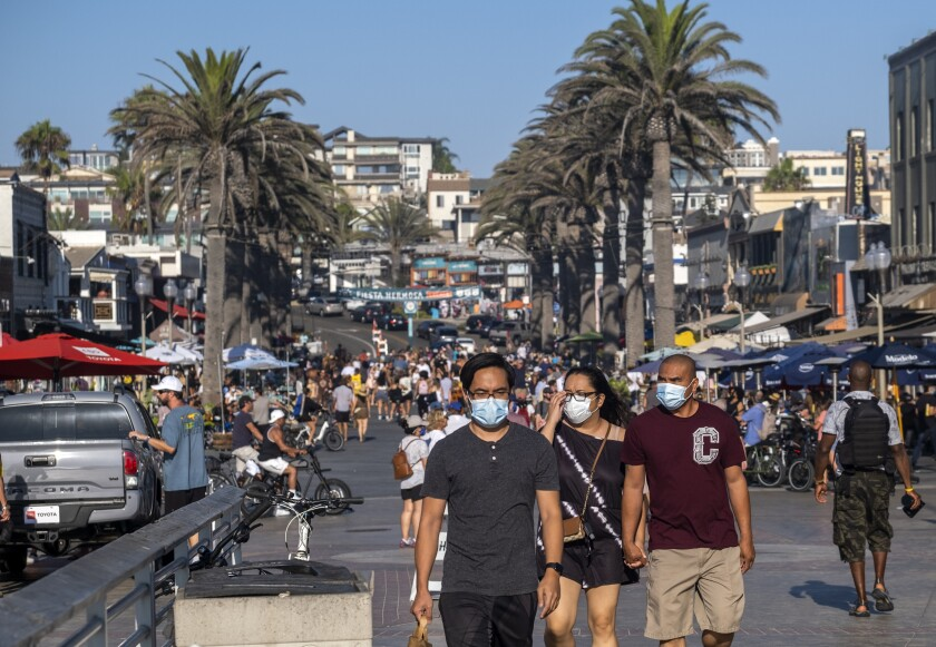 Crowds of people, some in masks, walk along a sidewalk bordered by palm trees.