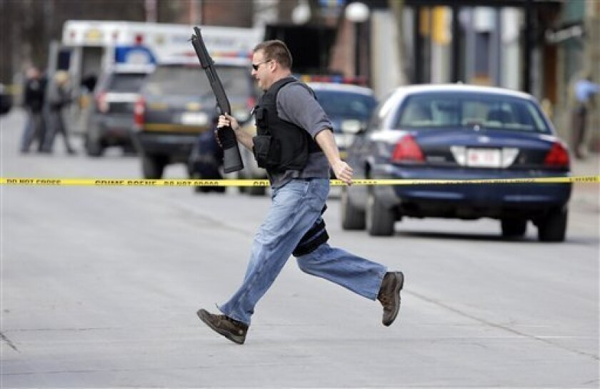 Law enforcement officers run for cover along Main Street  in Herkimer, N.Y., when shots were fired while they were searching for a suspect in two shootings that killed four and injured at least two on, Wednesday, March 13, 2013. Authorities were looking for 64-year-old Kurt Meyers, said Herkimer Po