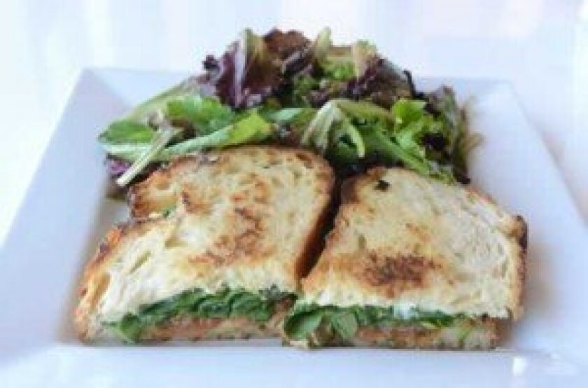 Farmer's Grilled Cheese consists of spring garlic-goat cheese spread, cheddar, grilled tomatoes and spinach on sourdough bread. Here, it's served with a side of organic green salad.