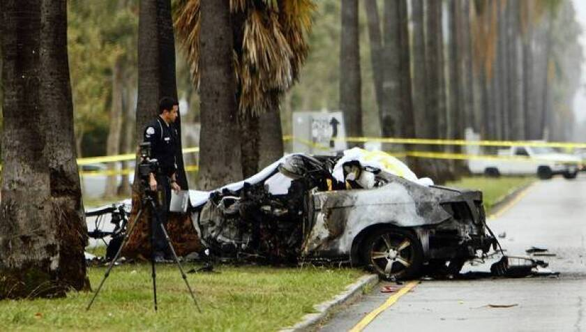 An LAPD officer investigates the scene of a burned out crash that killed journalist Michael Hastings.