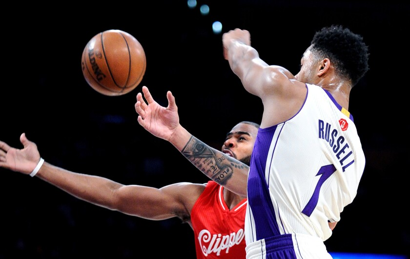 Guards Chris Paul of the Clippers and D'Angelo Russell of the Lakers try to track down a loose ball.