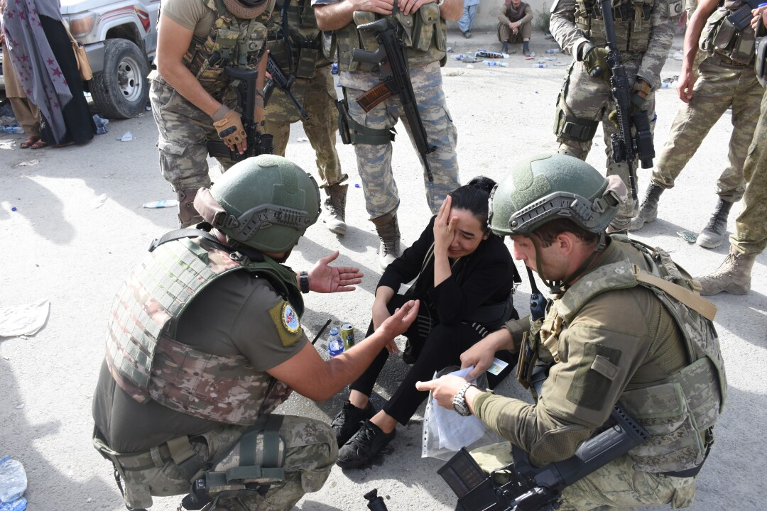 Turkish soldiers calm a woman down after she realized she lost her passport as people waiting for evacuation