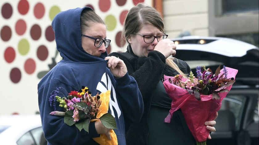 People place flowers, Sunday, Oct. 7, 2018, at the scene where 20 people died as the result of a lim