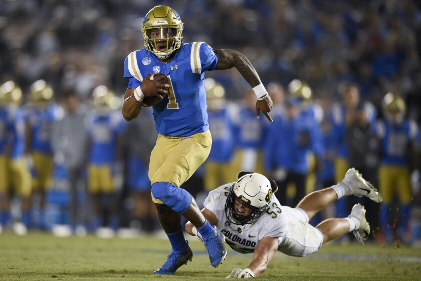 UCLA quarterback Dorian Thompson-Robinson, left, evades Colorado linebacker Nate Landman during the first half of their game on Nov. 2.