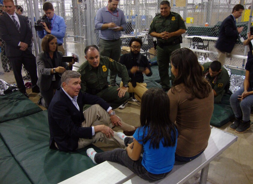 Border Patrol Commissioner R. Gil Kerlikowske, left, talks with a Salvadoran mother and her 6-year-old twins with the help of a Border Patrol agent's translation. Kerlikowske visited the processing center in McAllen, Texas, on Wednesday in an attempt to deter people from crossing the border.