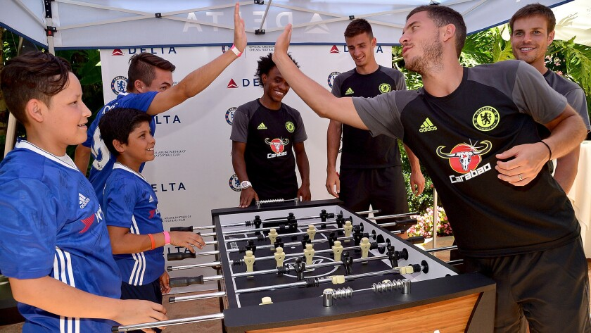 Chelsea's Cesar Azpilicueta high-fives Christopher Escobar during a foosball game on Wednesday.