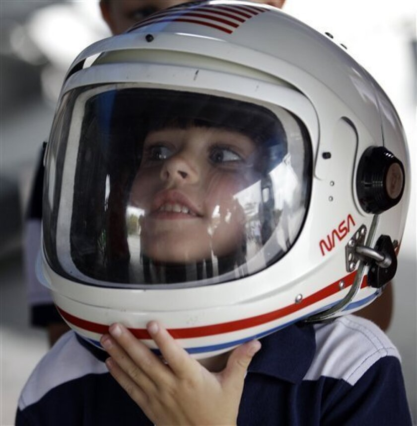 Xavier Ladik of Philadelphia tries on a helmet at the Kennedy Space Center Visitor Complex Thursday, July 7, 2011, in Cape Canaveral, Fla. The space shuttle Atlantis is scheduled to launch on Friday, July 8 and is the 135th and final space shuttle launch for NASA. (AP Photo/David J. Phillip)
