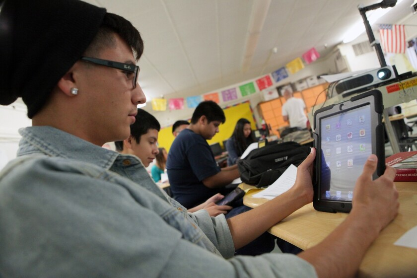Students at Theodore Roosevelt High School explore iPads provided by L.A. Unified, part of the district's $1.3-billion technology program.