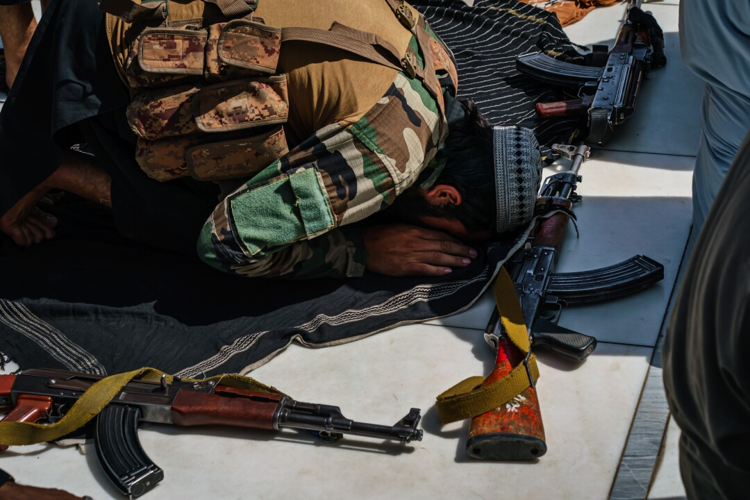 Taliban fighters pray with rifles by their sides