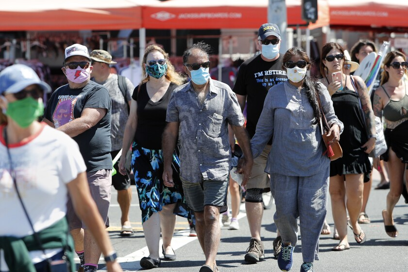 Beachgoers wear face masks to protect themselves as they walk  in downtown Huntington Beach on Saturday.