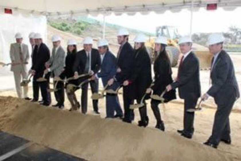 UC San Diego professionals, Mayor Bob Filner and the Altman family scoop the first shovels of dirt for the new institute.