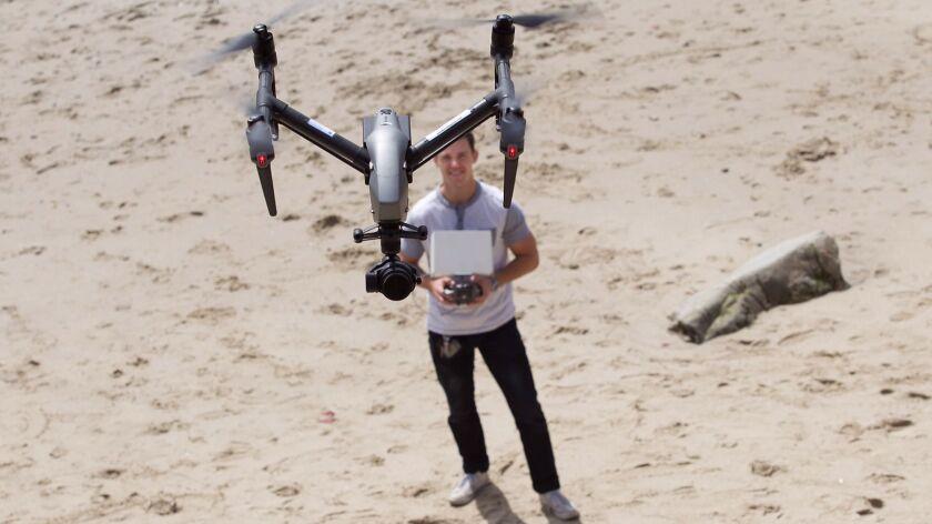Licensed drone pilot John Barrett flies his professional model camera drone above Rockpile Beach on