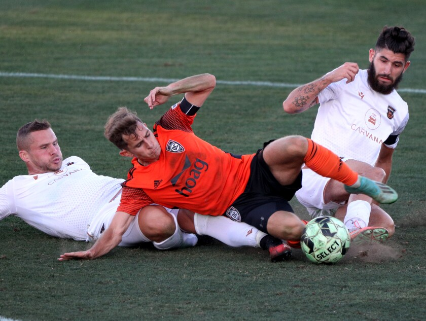 Orange County Soccer Club's Brian Iloski slides for the ball between two Phoenix Rising players.