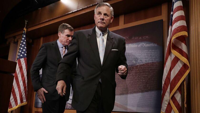 Sen. Mark Warner, left, and Sen. Richard Burr leave a news conference after discussing the Senate Intelligence Committee's upcoming work.