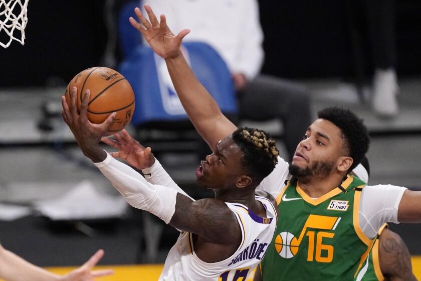El base de Los Lakers de Los Ángeles Dennis Schroder lanza el balón mientras lo defiende Juwan Morgan del Jazz