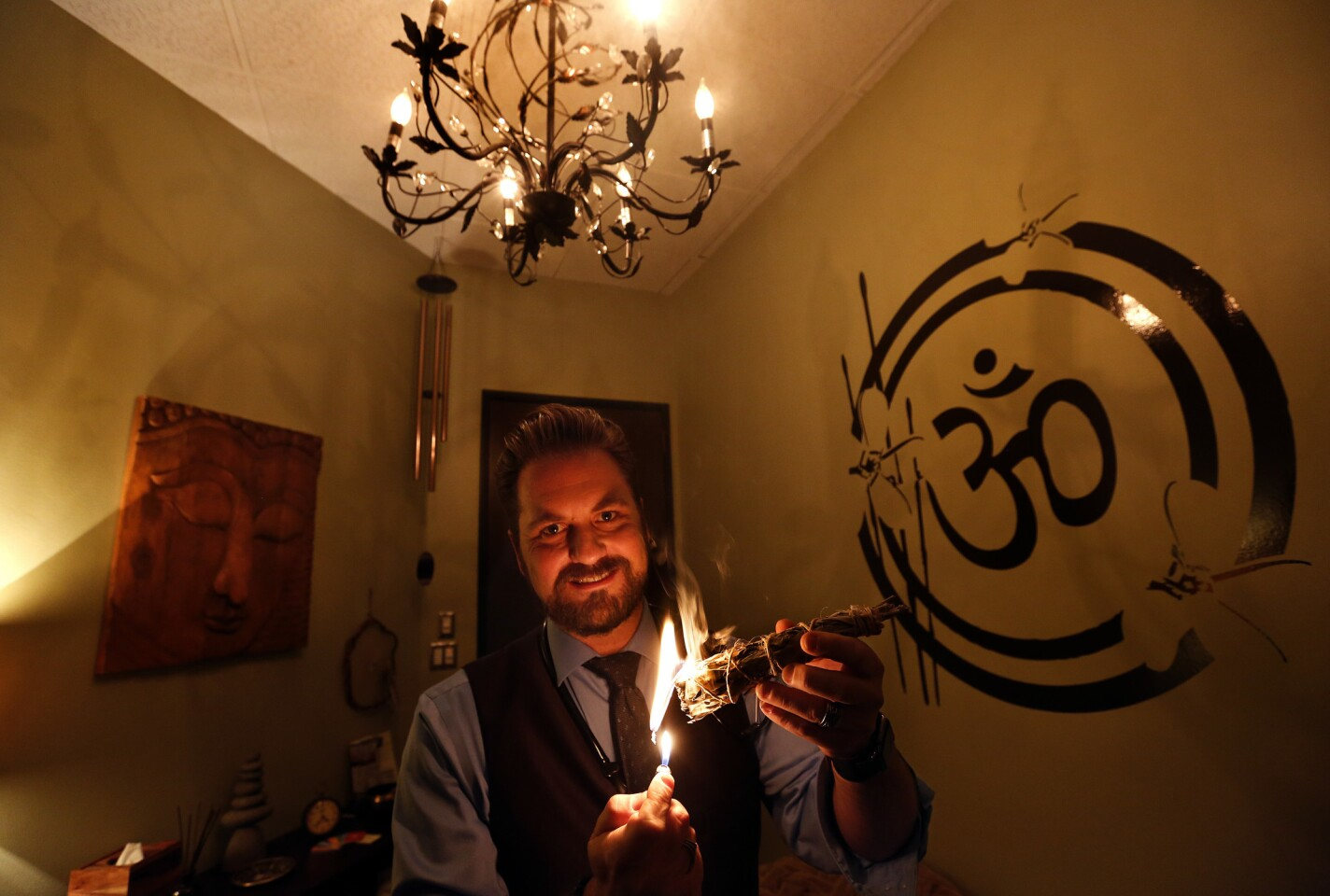 Dr. Michael Lewis of Willow Healing Center burns native white sage inside his office in Woodland Hills.